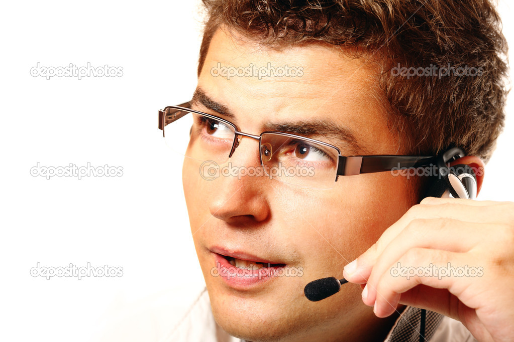 Young handsome worker with headset talking to a customer over white background