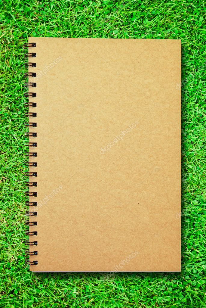 Brown cover notebook on green grass field