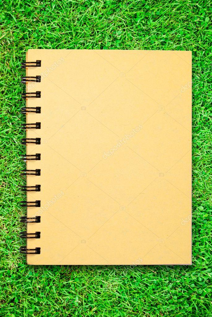 Small notebook on green grass field
