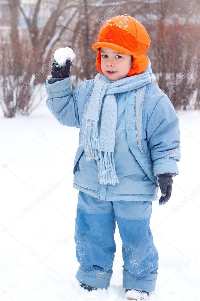 Little boy playing snowballs; snowman sculpts; digs snow;