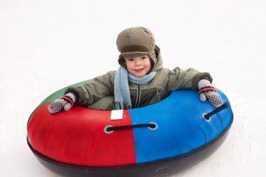 Winter walk; boy rides a Snowtubing; sleds; hill; playing snowba