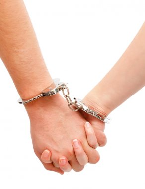 Couple's hands linked with handcuffs