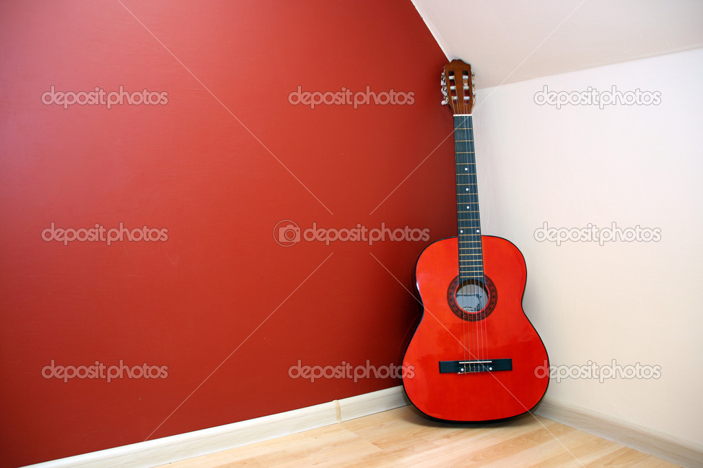 Acoustic guitar in room corner