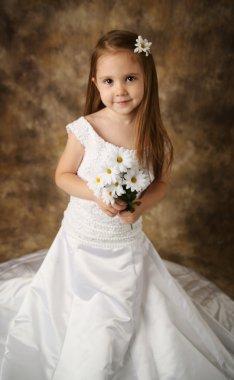 Little girl trying on mommy's wedding dress