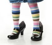 Fotografie Little girl trying on moms shoes
