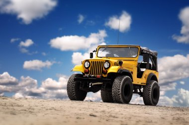 Photo of a Yellow Jeep at the beach