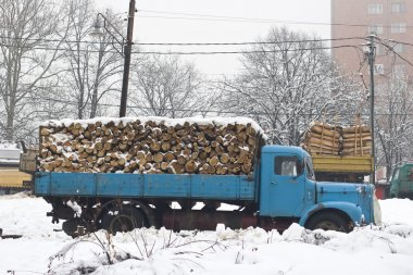 Old truck with firewood in the snow