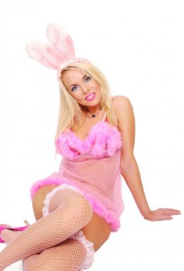 Playboy girl in a rose baby-doll and rabbit ears is sitting ot the floor