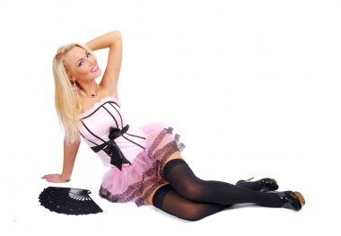 Pretty girl in a rose corset sit on the floor and keeps hand behind her hea