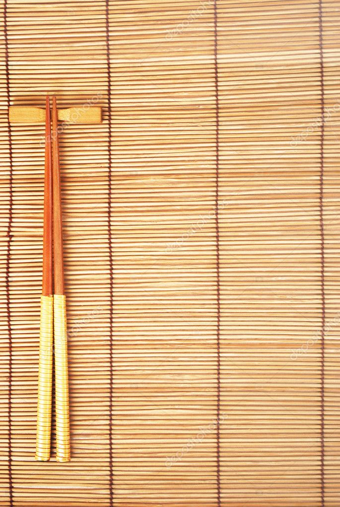 chopsticks on brown bamboo matting background u2014 photo by svtrotof