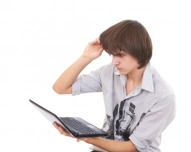 Teen looks to notebook and raises his glasses in surprize