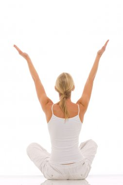 Woman dressed in white sitting cross-legged doing yoga