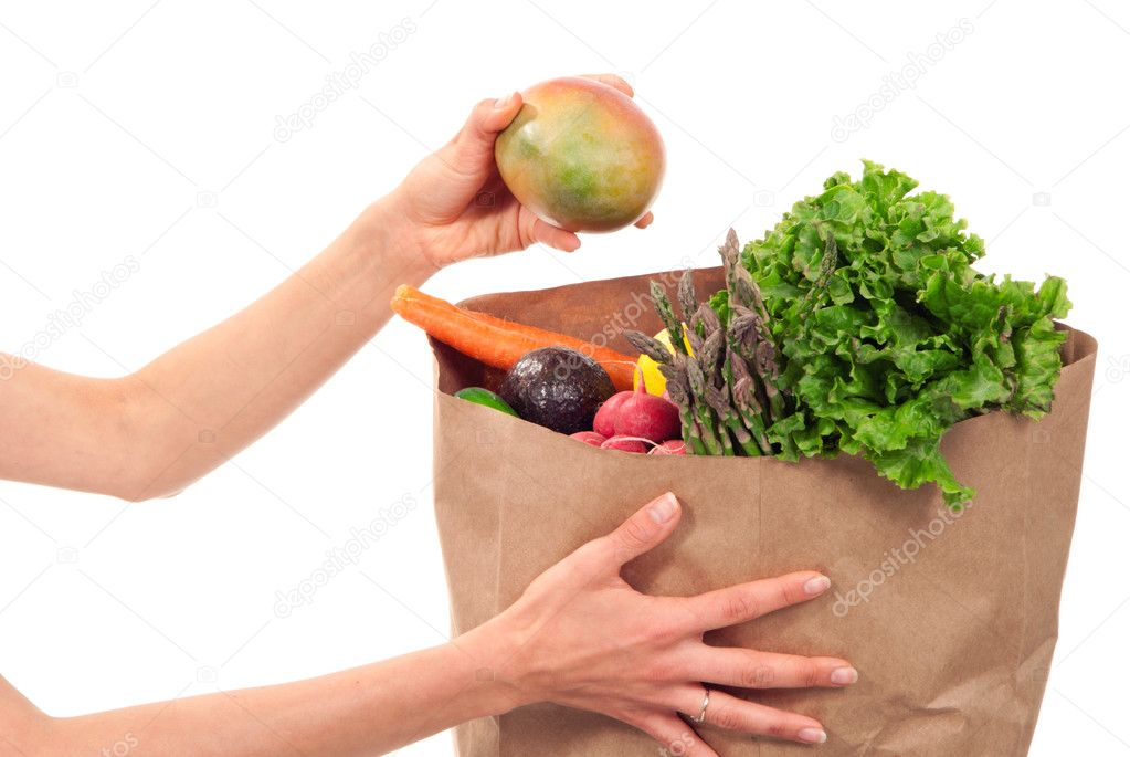 Hand holding bag full of fresh food items