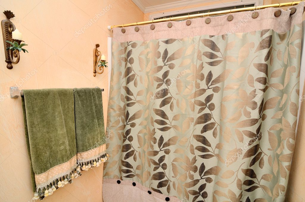 Towels near a shower curtain in a residential bathroom