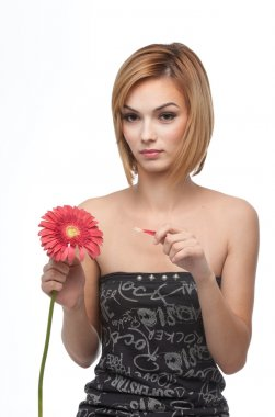 Portrait of a young woman picking pettals from a flower, looking