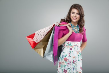 Young woman in colourful outfit holding a few shopping bags, smi