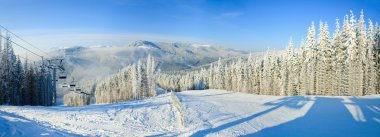 Winter mountain landscape with ski lift and skiing slope.