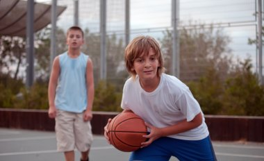 Kids play basketball in a school.