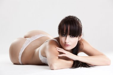 Female model in white lingerie laying on the ground