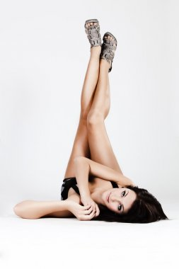 Young beautiful woman holding long legs up