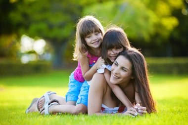 Young mother and two daughters playing outdoors