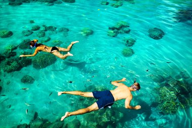 Young couple snorkeling in clean tropical water