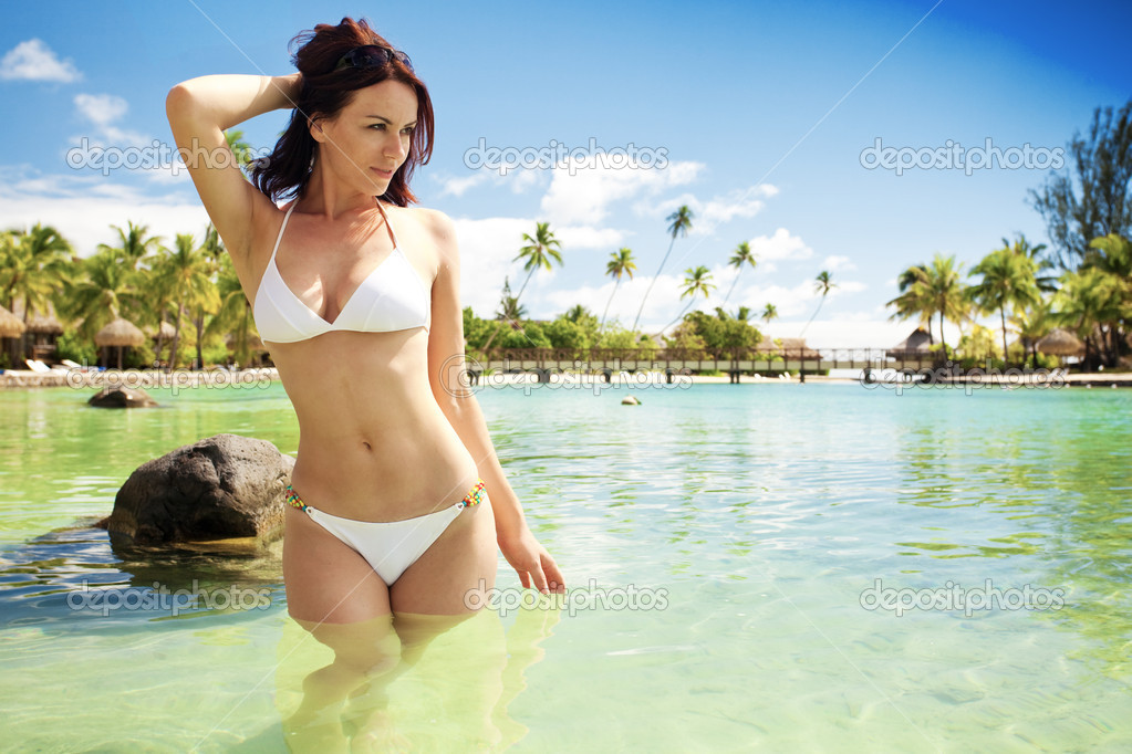 Young woman in white bikini standing next to beach
