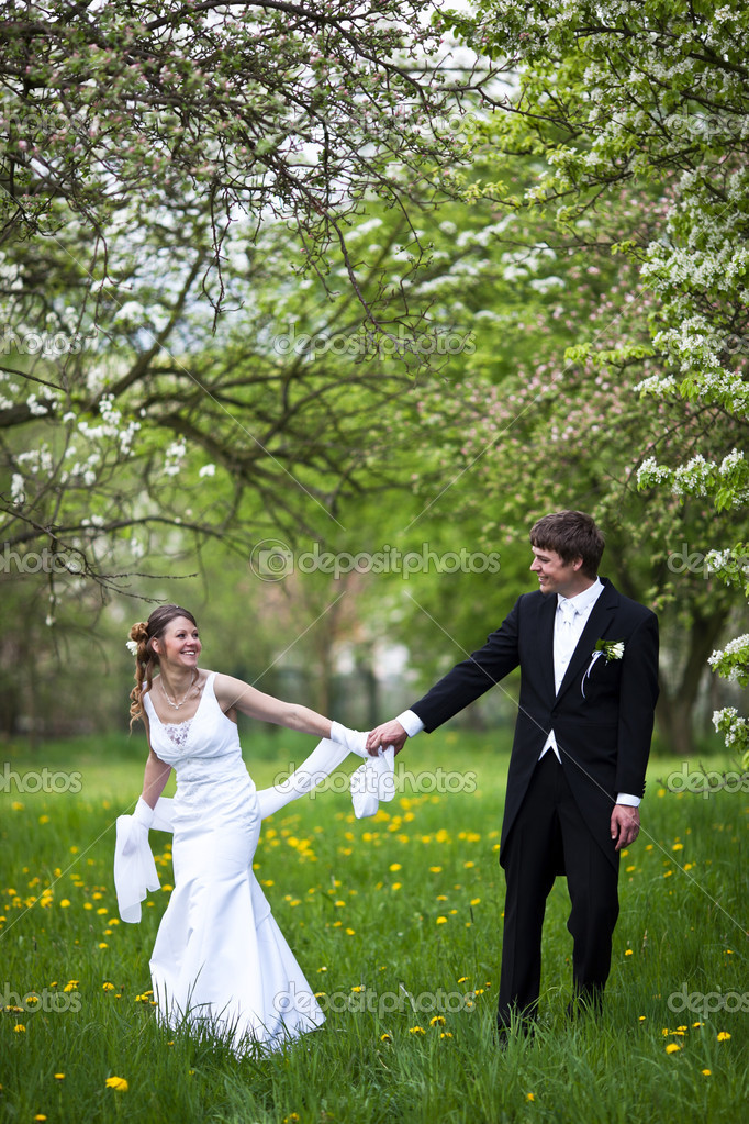 Young wedding couple - freshly wed groom and bride posing outdoo