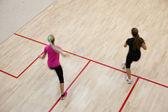 Dvě ženské squashové hráče v rychlou akci na squashovém kurtu (moti