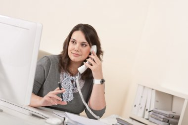 Young woman talking on the phone at office