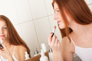 Body care series - Beautiful red hair woman applying lipstick