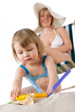 Mother with child playing with beach toys