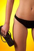 část ženského těla, na sobě černé bikiny a hospodářství klopný