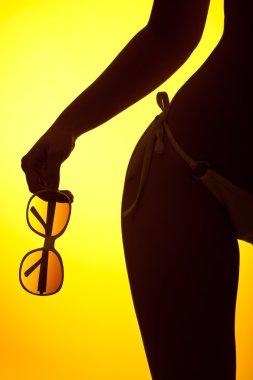 Silhouette of female body with bikini and sunglasses