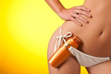 Part of female body with white bikini and bottle of suncream