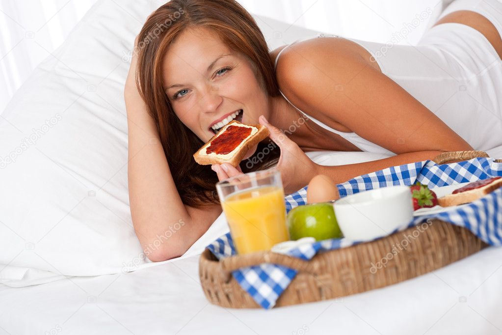 Young woman having home made breakfast in bed