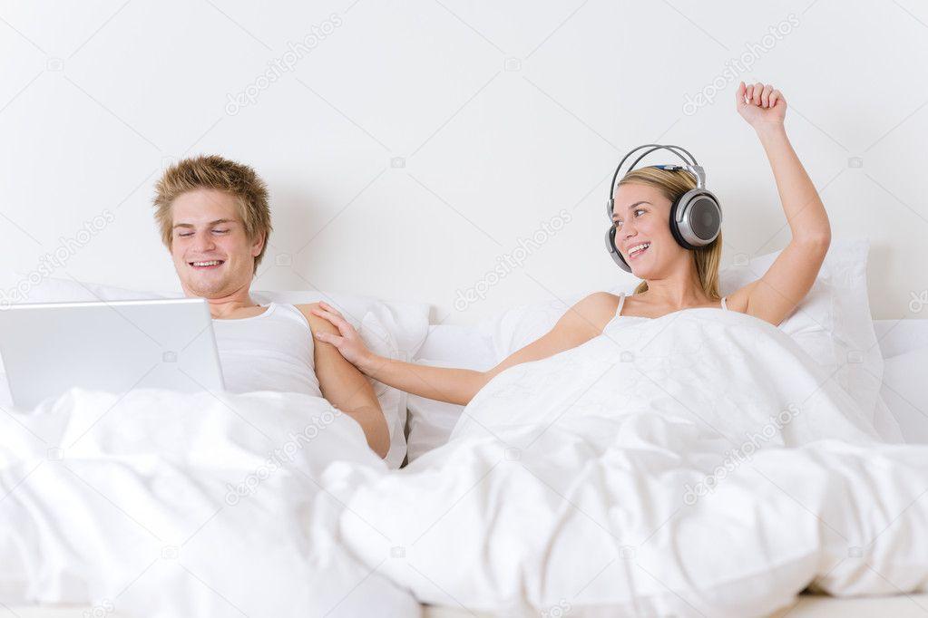 Jeune Couple Se Detendre Au Lit Avec La Musique Et Ordinateur