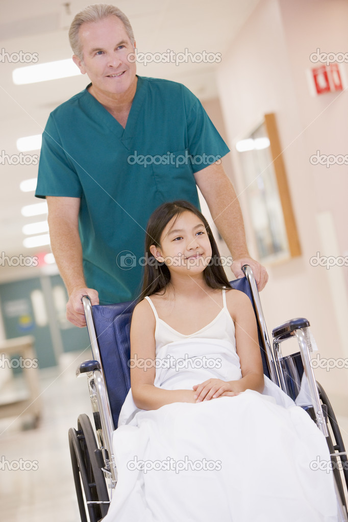 An Orderly Pushing A Little Girl In A Wheelchair Down A Hospital ...