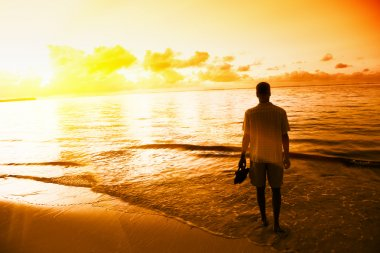 Young man and sunset on Caribbean sea