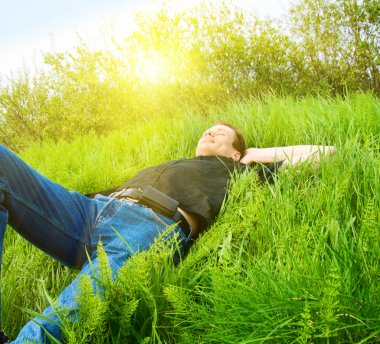 Young man relax in spring grass