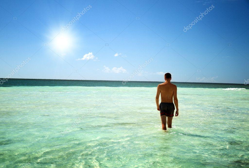 Young man walking in Caribbean sea