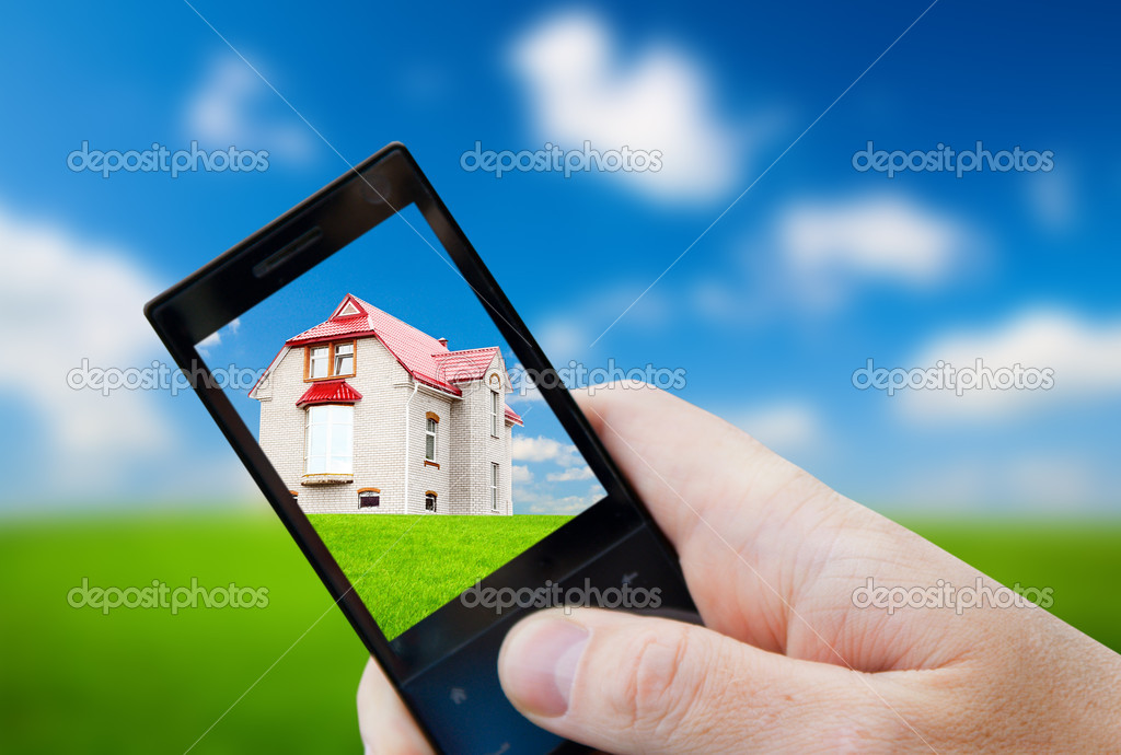 Cell phone in hand and house