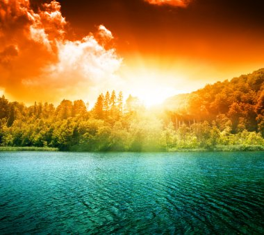 Green water lake in forest and sunset