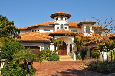 Spanish style home with tower, multiple roofs