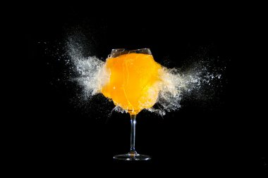Glass with orange juice explosions at the black background