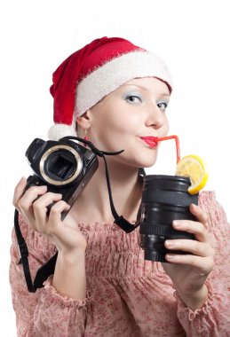 Beautiful girl drinking from lens cup in Christmas hat isolated