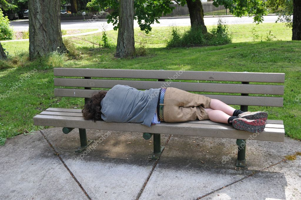 Sleeping on a bench in a public park
