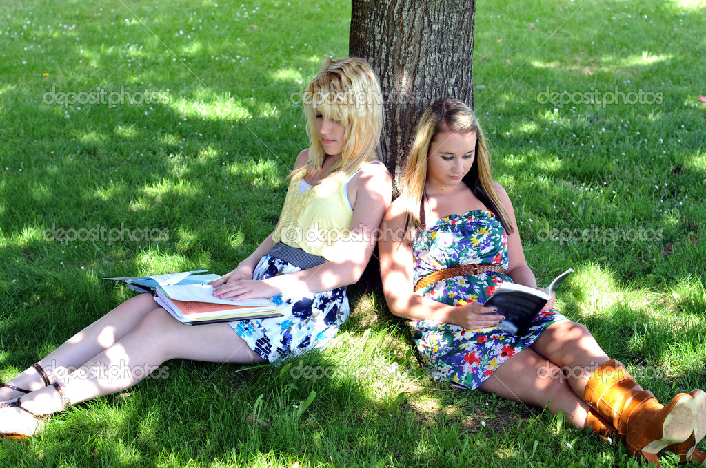 Girls reading books under tree in shade