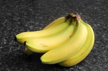 Bananas on a black kitchen counter top. stock vector