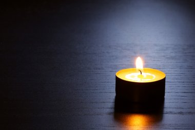 Single candle with back lit. Tranquil scene.